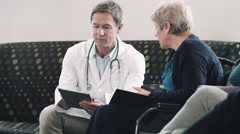 Doctor consulting patient in hospital waiting room Stock Footage