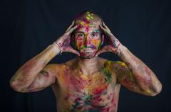 Handsome young man with skin all painted with Holi colors Stock Photos