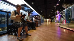 People use their phones or tablets at a free wifi area in the Siam Center Stock Footage