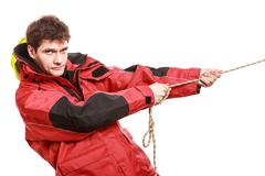Stock Photo of Young man sailor in red wind jacket. Sailing.