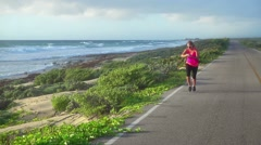 Woman running on sea coastal road Stock Footage