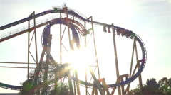 SLOW MOTION: Extreme roller coaster ride at golden sunset - stock footage
