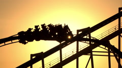 SLOW MOTION: Sunset sun shining through extreme roller coaster ride - stock footage