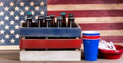 Fourth of July with beer and party items on rustic wood Stock Photos
