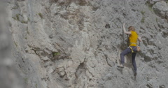 A female rock climber climbs up a rock Stock Footage