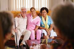 Portrait Of Nurse And Happy Old People In Hospice Stock Photos