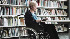 Disabled Senior adult female in wheelchair in library - stock footage