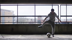 Wide shot of football player doing tricks with a ball in urban city environment Stock Footage