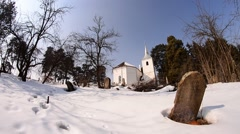 White church built in the middle of a pine envelope surrounded by a cemetery - stock footage