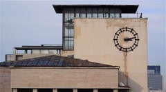 Passage of time marked by metal clock mounted on the wall of a building in do Stock Footage