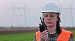 Businesswoman in hard-hat talking on walkie-talkie - stock footage