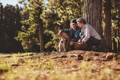 Mature couple using a compass on a hike - stock photo