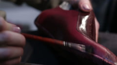 Painting the shoe leather. Shoemaker sews shoes - stock footage