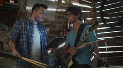 Band of musicians have a discussion in a garage studio while using a tablet Stock Footage