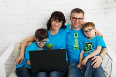 Family of four wearing eyeglasses with laptop Stock Photos