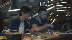 Two students are studying electronics and soldering in a garage Stock Footage