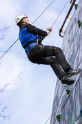 Man climbing up a wall in an exercise for mountaineering - stock photo