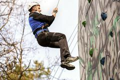Man climbing up a wall in an exercise for mountaineering Stock Photos