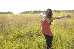 Young beautiful pregnant woman holding tummy smiling, in red a light summer - stock photo