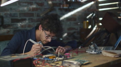 Student is studying electronics and soldering a circuit board in a garage - stock footage