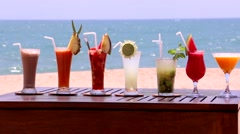 Glasses of brightly-colored cocktails against the backdrop of the ocean Stock Footage