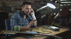 Young man is singing and making an audio recording at home in a garage Stock Footage