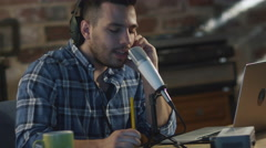 Young man is singing and making an audio recording at home in a garage - stock footage