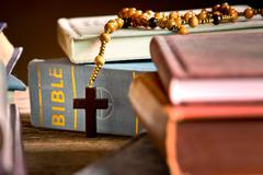 Books, bible and rosary in the bookcase Stock Photos