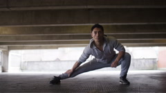 Young flexible man stretches deeply in urban city surroundings Stock Footage