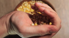 Man's hand pouring pop corn into a bowl Stock Footage