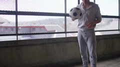 Young asian man casually bouncing a football, in slow motion - stock footage