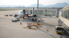 Laotian people loading baggage at Louangphrabang airport Stock Footage