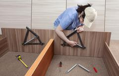 Stock Photo of Flat Pack furniture assembly and installation service, women handyman working