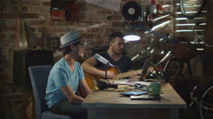 Two young man sing and play guitar while recording a song in a home studio Stock Footage