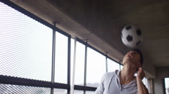 Young man doing headers with a football in urban environment - stock footage