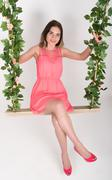Beautiful young leggy blonde in a little pink dress and red high-heeled shoes - stock photo