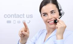 Contact us, customer service operator woman with headset smiling and touch ic Stock Photos