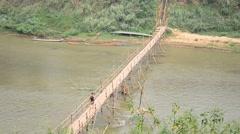 People walk on bamboo bridge crossing mekong river Stock Footage
