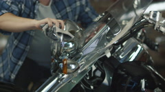 Man is cleaning and polishing chrome objects on his motorcycle in a garage - stock footage