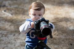 Young photographer child taking photos with camera on a tripod - stock photo