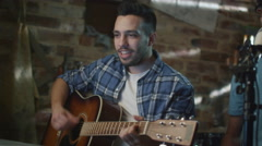 Band sing and play guitars while recording a song and practicing in home studio - stock footage