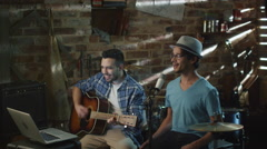 Two young man sing and play guitar while recording a song in a home studio - stock footage