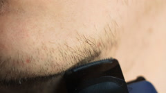 Man shave chin with electric shaver in slowmotion Stock Footage