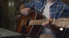 Man plays guitar while rehearsing a song in a home studio in a garage - stock footage