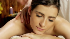 Dolly shot to closeup of woman getting back massage in spa 4K warm color corr Stock Footage