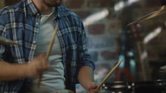 Drummer plays music while rehearsing a song in a home studio in a garage - stock footage