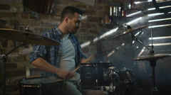 Drummer plays music while rehearsing a song in a home studio in a garage Stock Footage