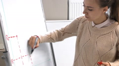 Young girl student draws the graph on a flipchart Stock Footage