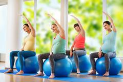 Happy pregnant women exercising on fitball in gym Kuvituskuvat