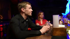 Cheerful man sitting at the bar. drinking alcohol from a stack Stock Footage
